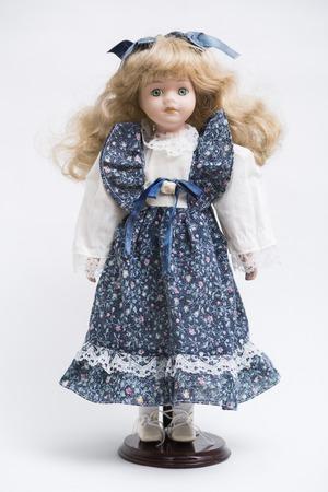 Portret lalki vintage z porcelany ceramicznej o zielonych oczach, falowanych blond włosach w starej niebieskiej sukience tekstylnej z delikatnym kwiatowym nadrukiem, w białej koszuli z haftowanymi białymi butami na białym tle.