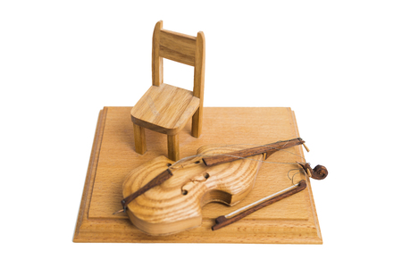 Old vintage wooden broken retro small yellow violin on stand with chair on isolated white background.