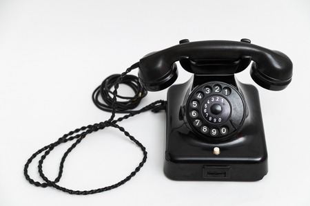 Old vintage stationary black telephone with dial and a tube Stock Photo