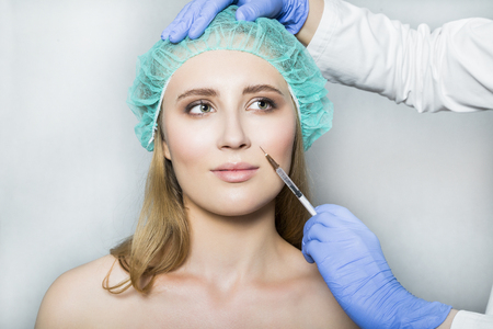 Doctor aesthetician makes face beauty injections to female patient Stock Photo