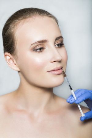 augmentation: Doctor aesthetician makes lips correction and augmentation to female patient