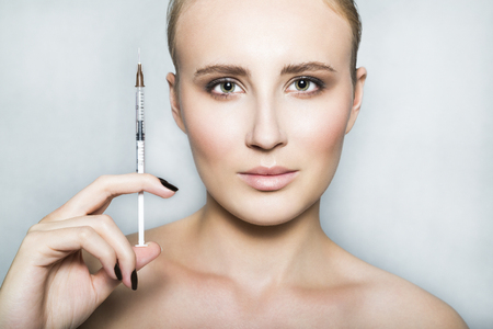Nude young female patient holds a syringe in her hand Stock Photo