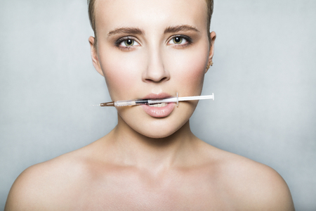 Nude young female patient holds a syringe in her mouth
