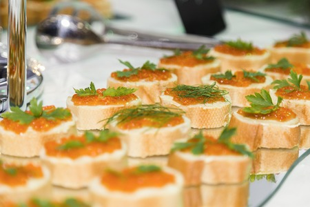 sandwiches of white bread with butter and red caviar lie in a row on a glass tray