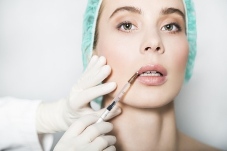 Doctor aesthetician makes hyaluronic acid beauty injections in lips to make lips correction and augmentation of young female patient in a green medical cap