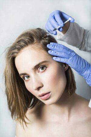 calvicie: Doctor aesthetician in blue medical gloves makes hyaluronic acid rejuvenation beauty injections in the back of the head of female patient for hair growth and to prevent boldness. Foto de archivo
