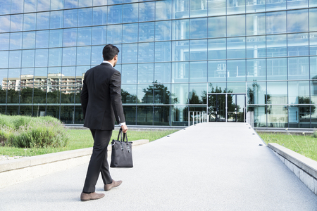 Anonymous businessman or worker in black suit with leather handbag or laptop case in his hand goes to work on the road to the entrance of a glass office building. 免版税图像