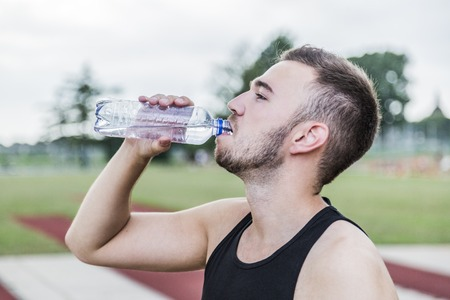 Athlete in black clothes drinking fresh water from transparent bottle on running track in summer day 写真素材
