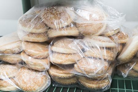 흰색 반죽 햄버거에 대한 원시 냉동 빵은 레스토랑이나 카페의 부엌에있는 냉장고에 투명 비닐 봉지에 포장. 스톡 콘텐츠