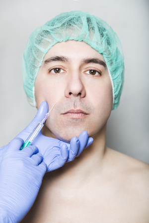 Doctor aesthetician makes hyaluronic acid rejuvenation beauty injections in the cheek of male patient in a green medical cap