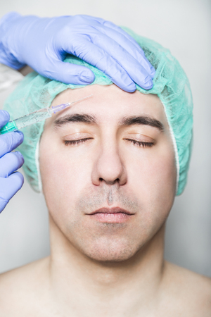 Doctor aesthetician makes hyaluronic acid rejuvenation beauty injections in the forehead of male patient with closed eyes in a green medical cap