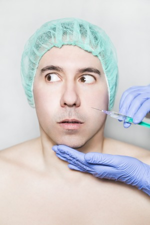 Doctor aesthetician makes hyaluronic acid rejuvenation beauty injections in the cheek of male patient in a green medical cap. Patient is looking away with mistrust and fear. He is afraid of syringe.