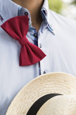 Man in a blue shirt with an untied red bow-tie with a white wicker hat with black band.