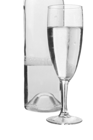 BARWARE: A bottle half-filled with water and a glass with water on white background.