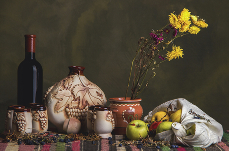 Ethnic folklore table covered with national balkan carpet with sweet red wine, ethnic ceramic clay jug and ceramic clay glasses, sliced green apples in a white towel and field flowers in a jug.