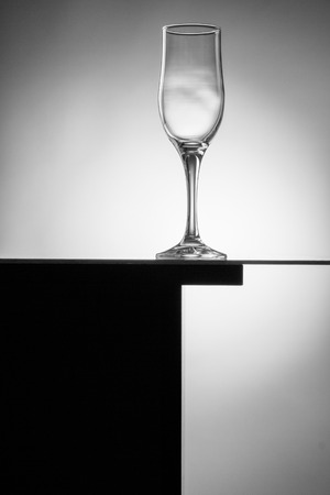 BARWARE: Black and white abstract composition with an empty wineglass on a table. Stock Photo