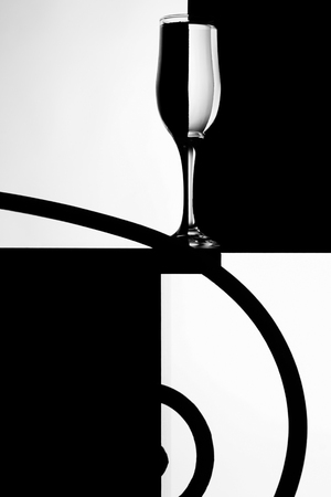 BARWARE: Black and white abstract composition with an empty wineglass on a table. Background as a chess table. Stock Photo