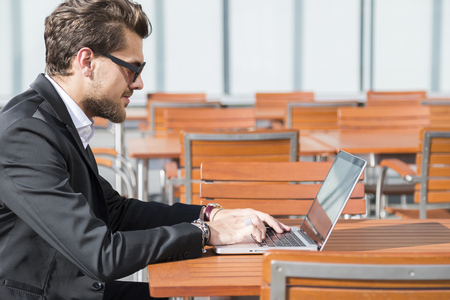 Male businessman or worker with beard and sunglasses in black suit with shirt, bracelets and accessories on hands sitting outside at a wooden orange table at a cafe and typing and working on computer.