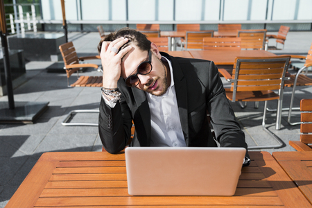 Male angry irritated in perplexity businessman or worker in sunglasses and black suit sitting outside at a wooden orange table in cafe near broken computer, holding phone. Stock Photo