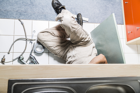 Specialist male plumber repairs faucet in kitchen Banque d'images