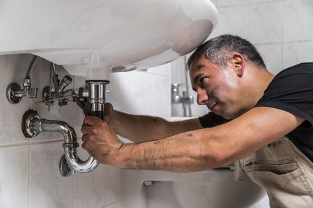 specialist male plumber repairs faucet in bathroom