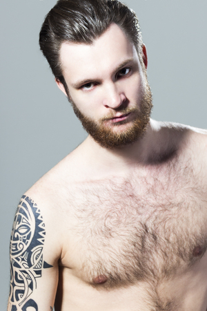 Brutal muscular sexy inked hairy unshaved young man with tattoo on his shoulder and beard Banque d'images