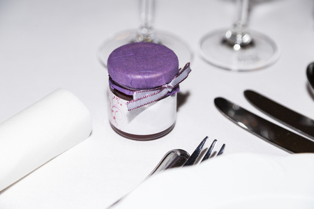 Jar of decorated confiture standing at wedding party table close-up Stock Photo