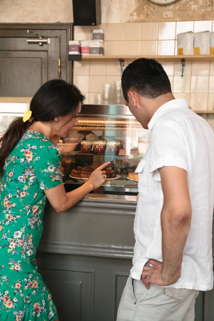 Young woman shows her husband sweets on showcase