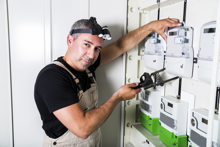 Electrician testing equipment in fuse switch box close up