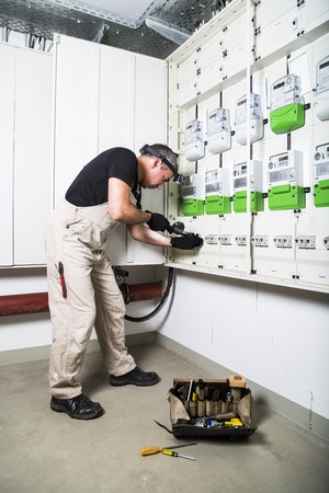 Electrician with box of tools testing fuse box or switch box by measuring device Stockfoto