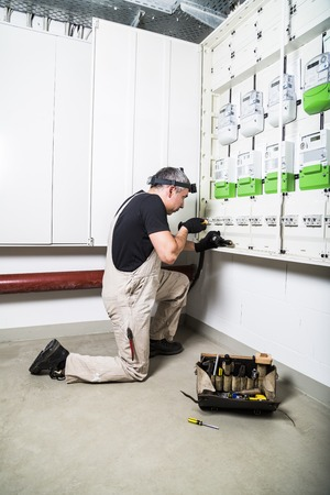Electrician with box of tools fixing fuse box or switch box