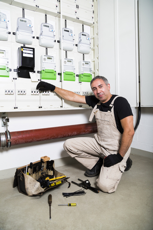 Electrician with box of tools near distribution or fuse board