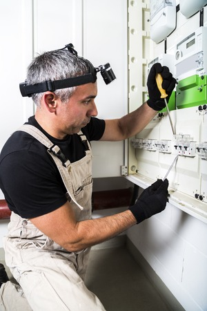 Electrician engineer works with screwdriver on fuse switch box close up