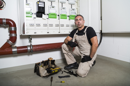 Electrician with box of tools seating near distribution or fuse board