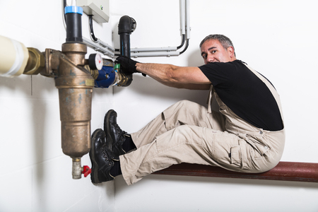 Plumber near water pipes opening water tap