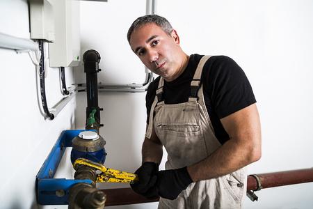 Plumber repairing metallic water pipes with manometer