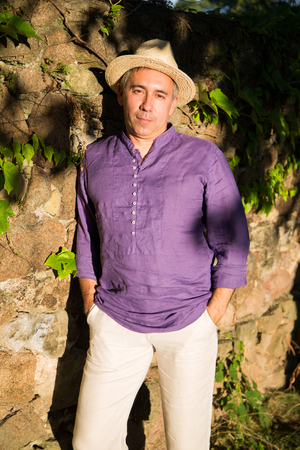 Man in linen shirt and straw hat stands near stone wall