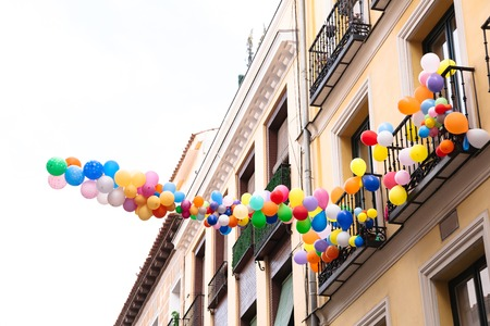 Bunch of colorful balloons in sky tethered to balcony