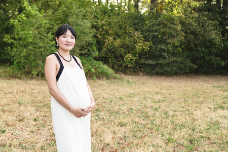 Beautiful pregnant asian woman standing in park outdoor 免版税图像