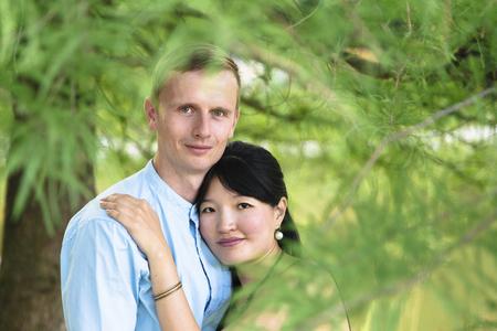 Romantic interracial couple in beautiful park outdoor in hugging Banco de Imagens