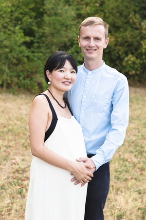 Asian pregnant women hugging with caucasian man outdoor