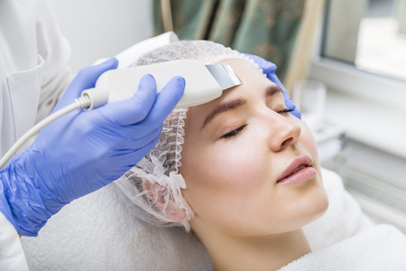 Cosmetologist makes ultrasound cleaning procedure in salon