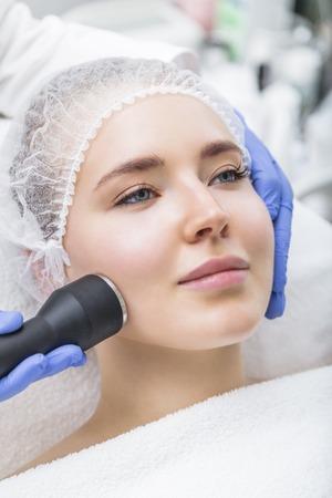 Beautician makes ultrasound massage procedure on female face