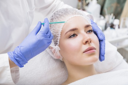 Young woman patient receiving plastic surgery injection