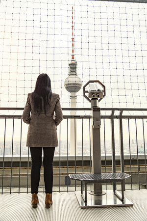 Fernsehturm Television Tower in Berlin, Germany. Girl looking at it and standing near telescope on observation deck 写真素材 - 118664395