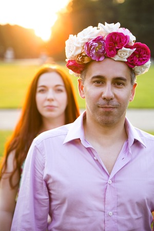Couple fooling around with flowers wreath oudoors
