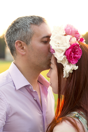 Man kissing woman in flower wreath on her head
