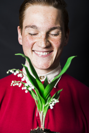 Man holding lily of valley and smiling at camera