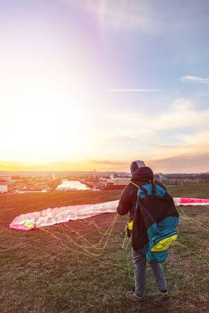 Landed man folds parachute lying on green grass Stock Photo