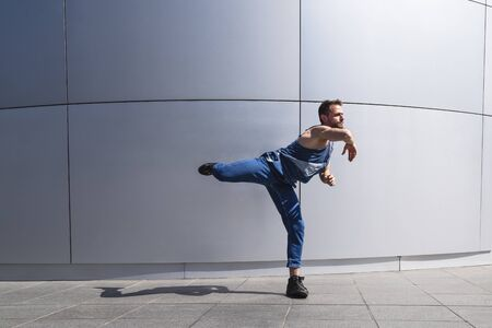 Young man street dancer dancing on wall background